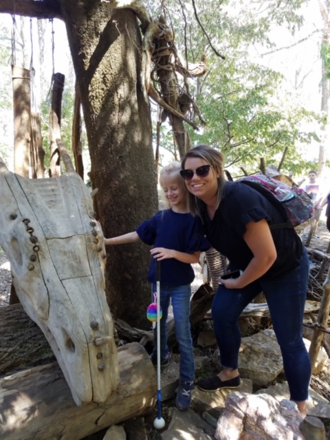 Brittany Clarkson with daughter Addy in a park, Addy touching a tactile wooden sculpture that resembles a dragon