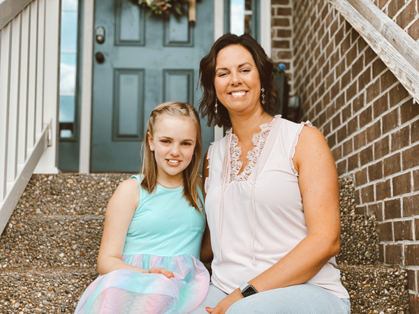 Mother with arm around daughter smiling sitting on front porch