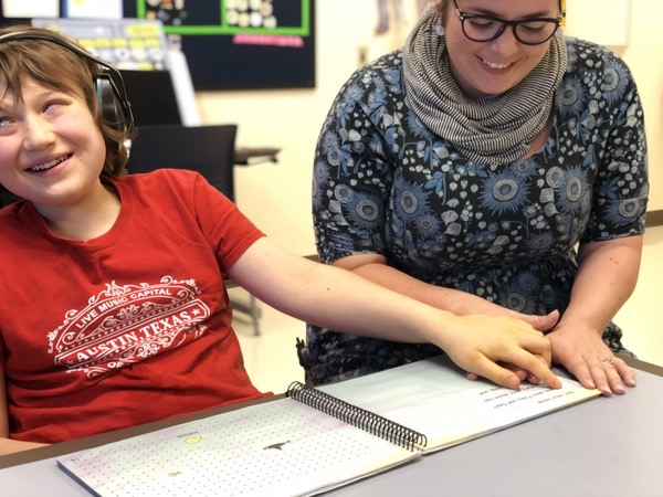 "Eddie is sitting next to his teacher, Julie, reading APH's ""Splish the Fish"" in braille using hand-under-hand while both are smiling."