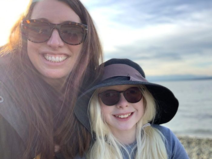 Mother and daughter smiling for camera, both wearing sunglasses, daughter wearing big floppy hat