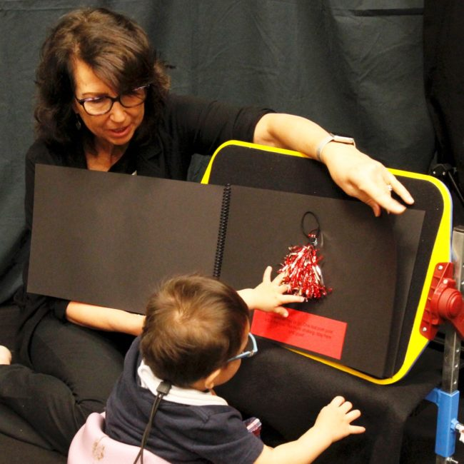 Teacher placing bright red objects on black board with child facing away from camera looking at the board