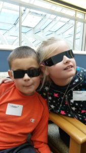 Two children at an eye doctor's appointment smiling and wearing disposable sunglasses.