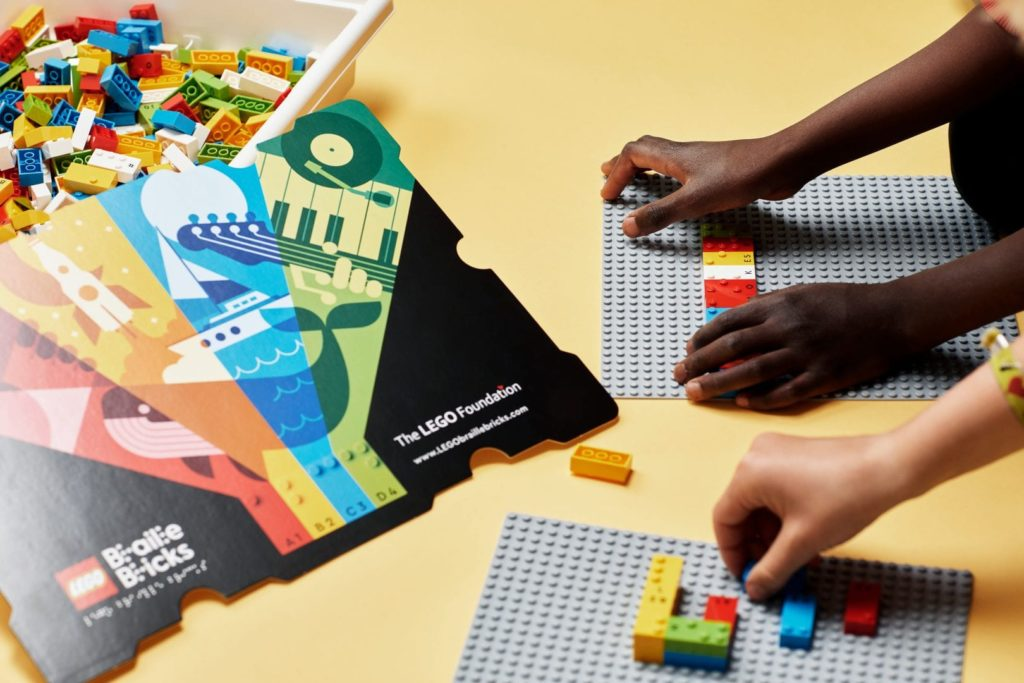 Children's hands playing with braille Lego bricks
