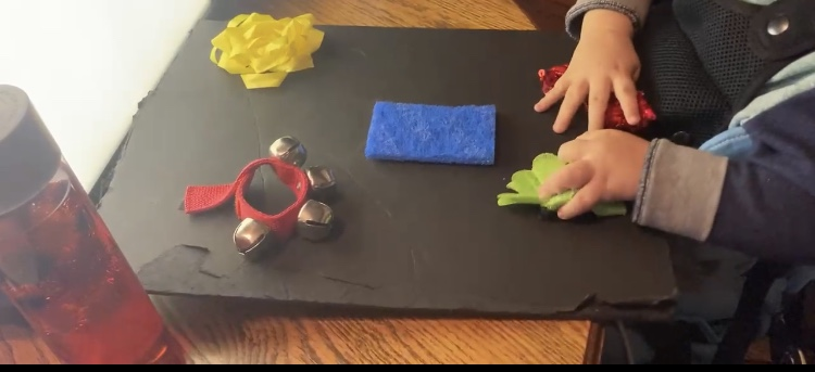 A photo of a toddler's hands exploring several household objects on a tabletop.