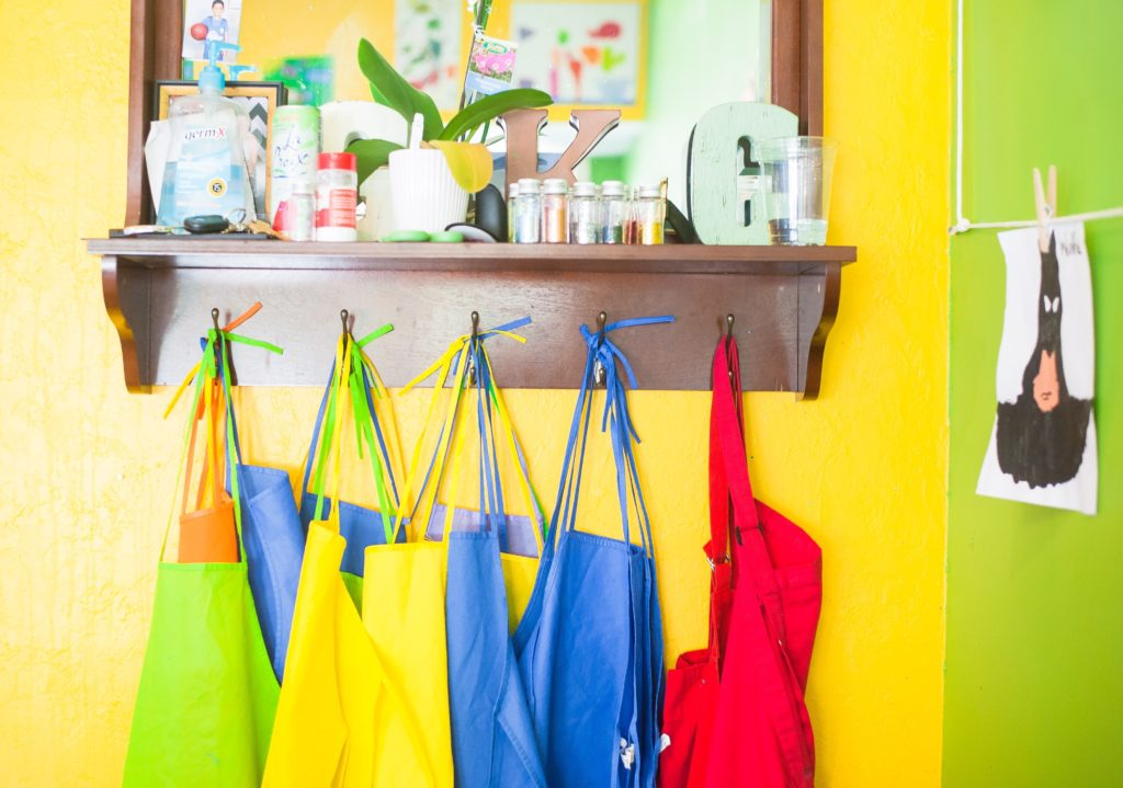 coat rack with colored tote bags hanging