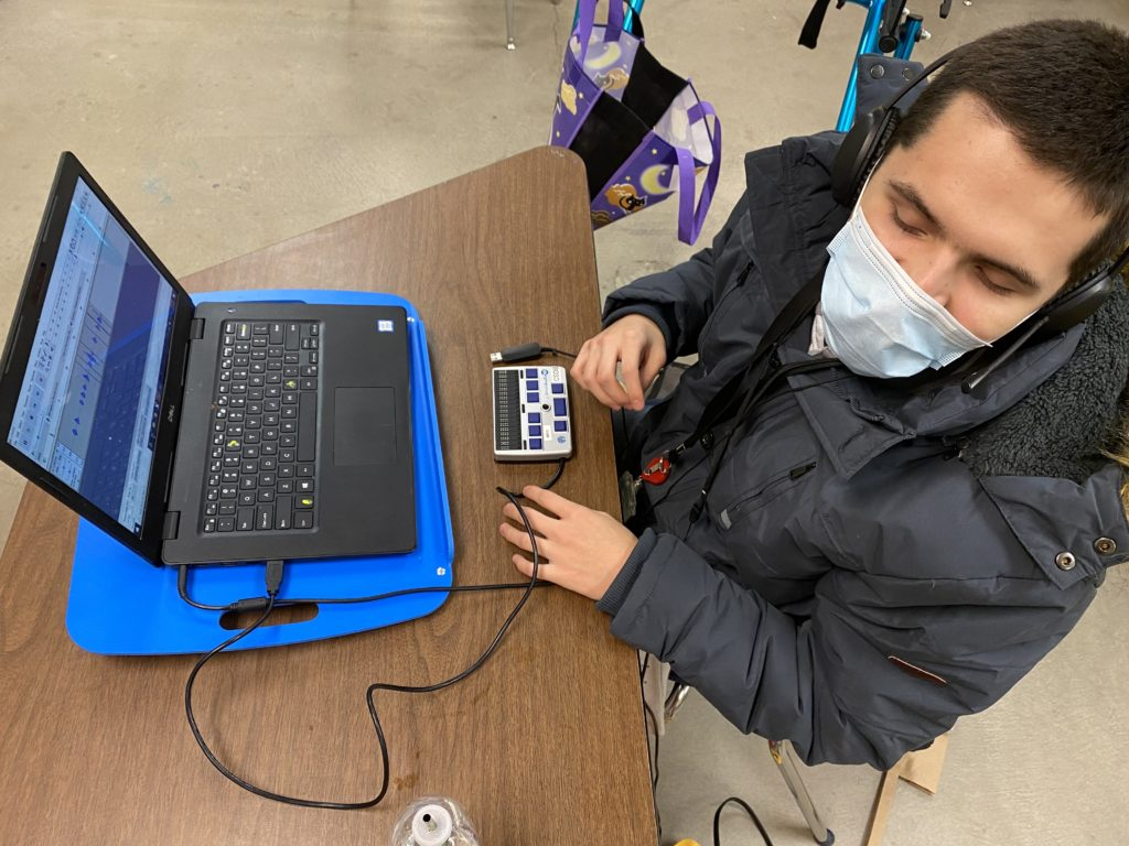 Teenaged boy sitting with mask on at a computer with a braille display