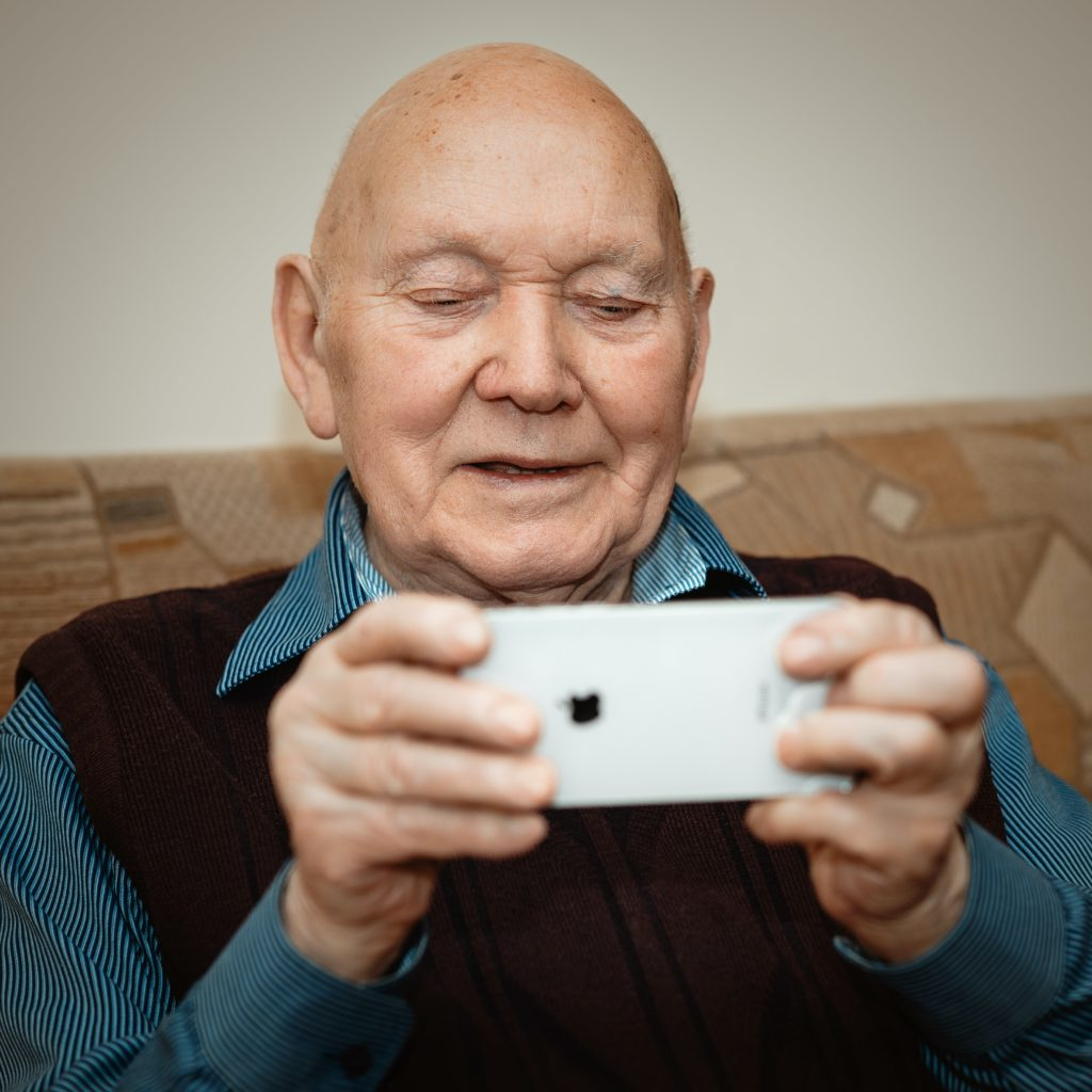 Senior adult holding a cell phone smiling