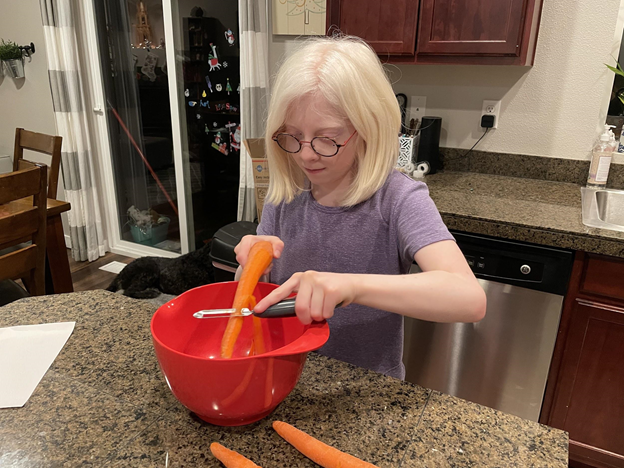 Young girl with glasses peeling a carrot into a bowl.