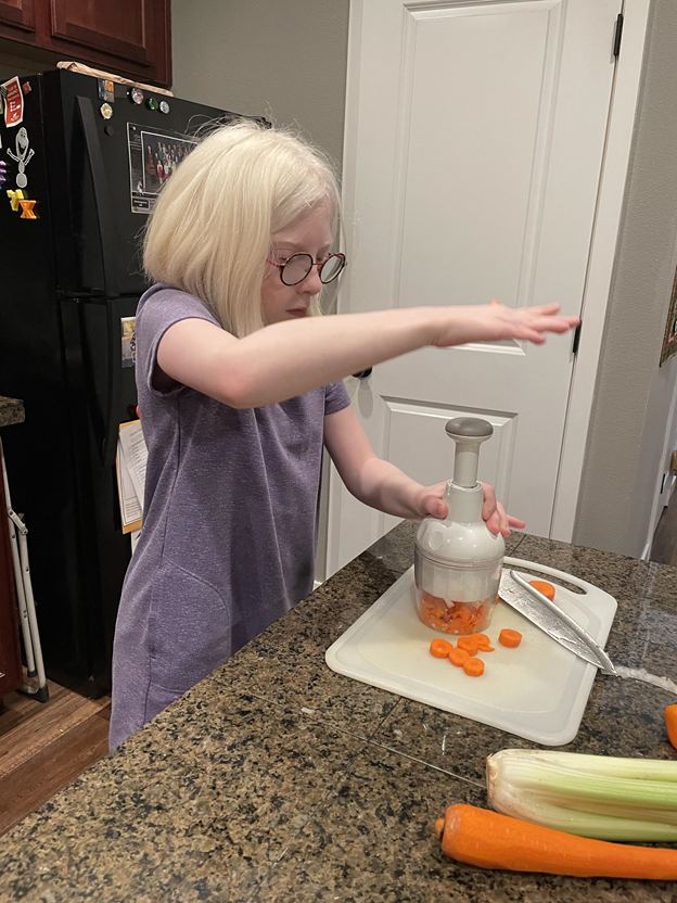 Young girl with glasses using a chopping tool to chop carrots,