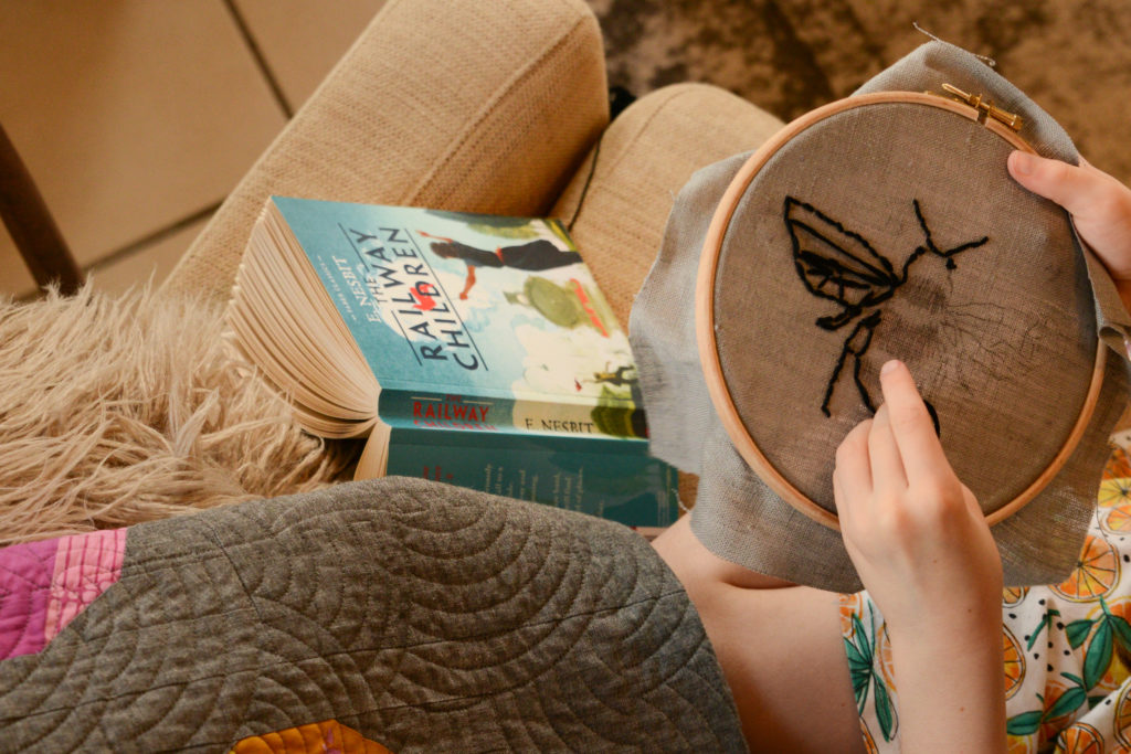 image of a child sitting on a sofa with a copy of The Railway Children cracked open with the pages down and the spine and cover facing up.  The child has switched from reading to working on an embroidery hoop with in the pattern of a bee.