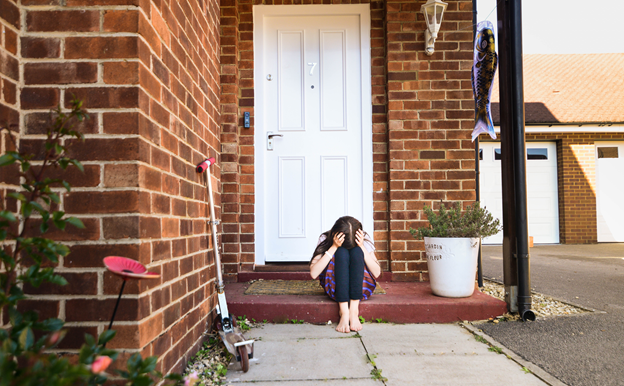 An upset child is sitting on the step in front of their home. The child is holding their head in their hands and resting their forehead on their knees.