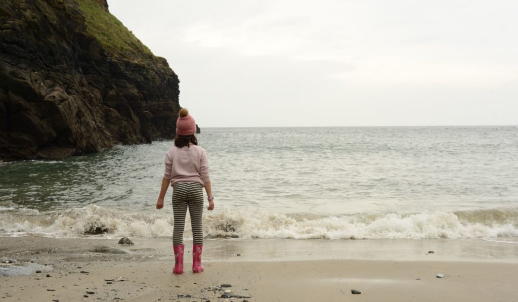 Young child in a knit cap, sweatshirt, and rain boots is standing on the edge of the ocean looking out at the ocean as waves roll up at her feet.