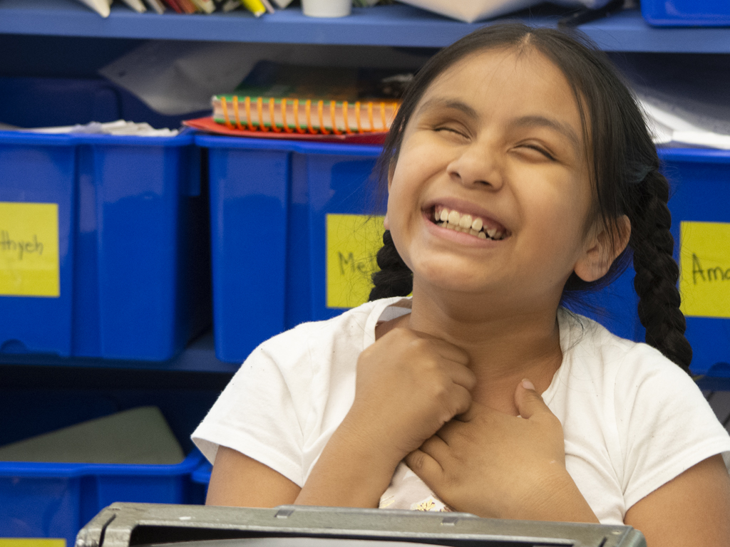 Young blind girl smiling with hands together