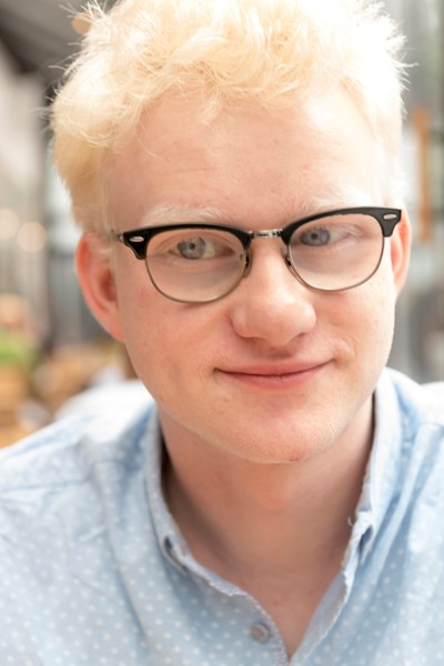 """""""Emmet Today"""" - a young man with short blond hair, light blue eyes, and glasses sits facing the camera with a confident yet understated smile on his lips"""