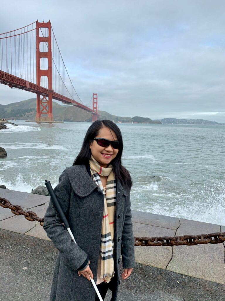 Image of Author Ann Wai-Yess Kwong posing with San Francisco Golden Gate Bridge behind her.