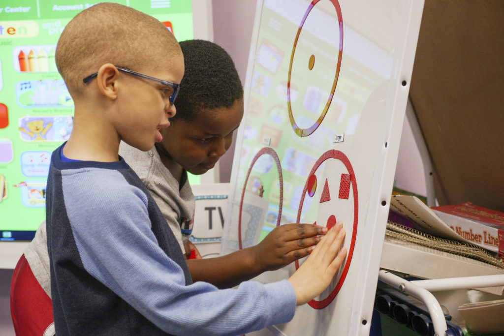 Two young boys playing with red magnets on a white board