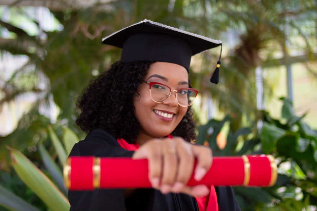 Girl wearing red glasses with cap and gown on. holding out red diploma