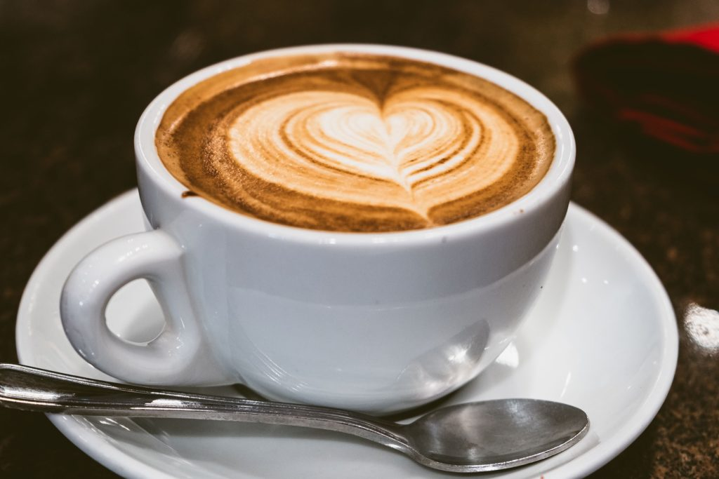 Latte in white cup on white saucer with a silver spoon