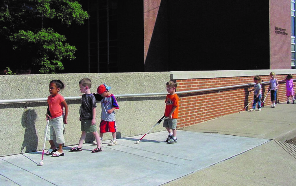 A group of children walking outside along a brick wall using white canes.