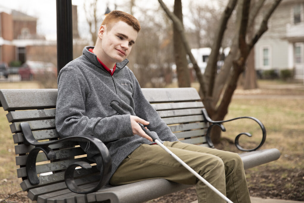 A young man sitting on a park bench hold his white cane.
