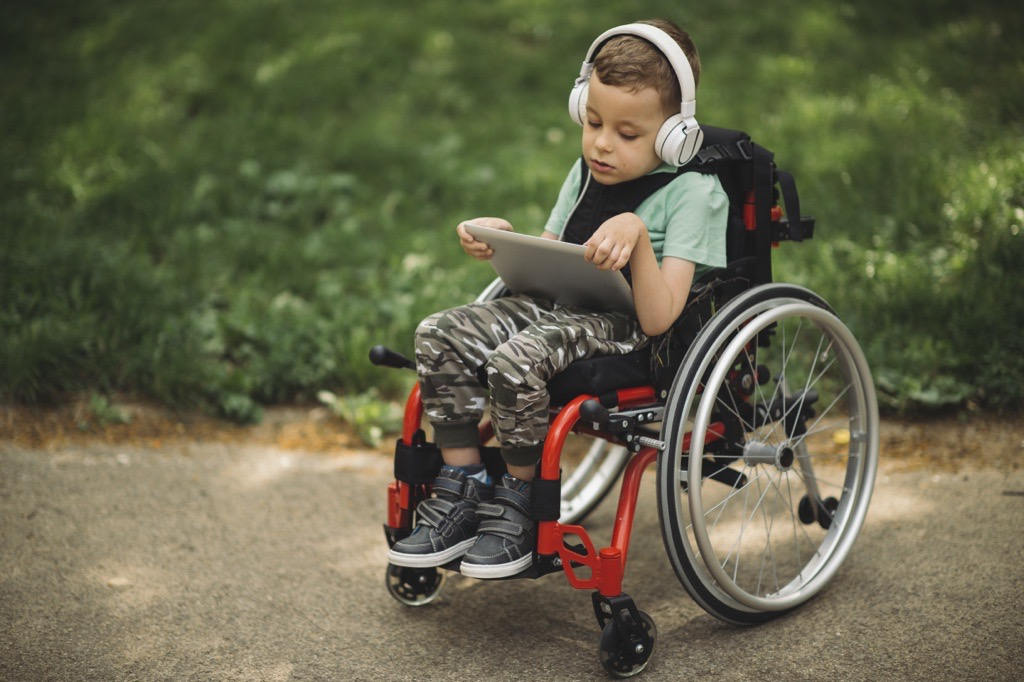 Young child in a wheelchair holding a tablet and wearing headphones.
